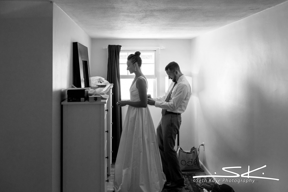 groom helping bride get ready