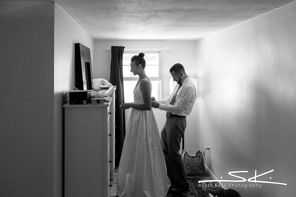 groom helping bride get ready