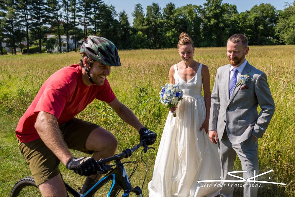 bicyclist interrupting bride and groom walking